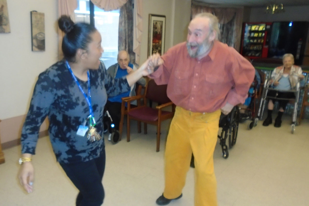 A staff member and resident having fun dancing